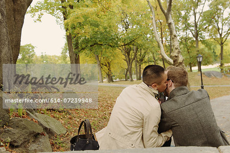 Man kissing partner on cheek in park Stock Photo - Premium Royalty-Free, Image code: 614-07239948