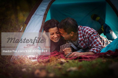 Mature couple lying together in tent, playing card game Stock Photo - Premium Royalty-Free, Image code: 614-07239969