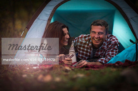 Mature couple lying together in tent, playing card game Stock Photo - Premium Royalty-Free, Image code: 614-07239970