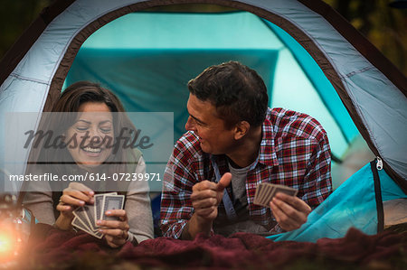 Mature couple lying together in tent, playing card game Stock Photo - Premium Royalty-Free, Image code: 614-07239971