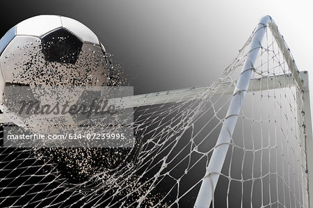 Studio shot of football powering through goal netting Stock Photo - Premium Royalty-Free, Image code: 614-07239995