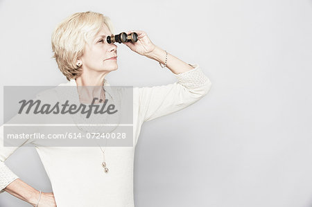Studio portrait of senior woman looking through binoculars Stock Photo - Premium Royalty-Free, Image code: 614-07240028