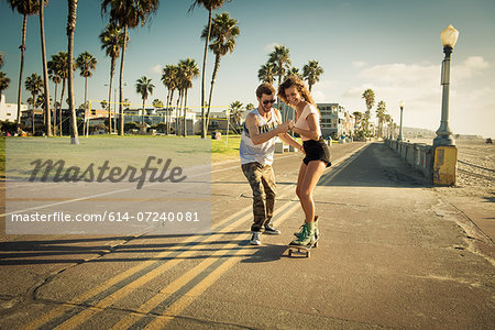 Young woman on skateboard at San Diego beach, boyfriend helping Stock Photo - Premium Royalty-Free, Image code: 614-07240081