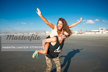 Young woman on boyfriend's back with arms raised Stock Photo - Premium Royalty-Free, Image code: 614-07240083