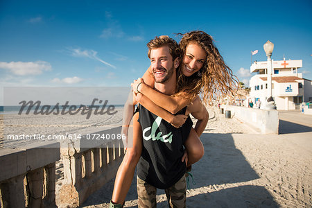 Young man giving girlfriend a piggy back at San Diego beach Stock Photo - Premium Royalty-Free, Image code: 614-07240086