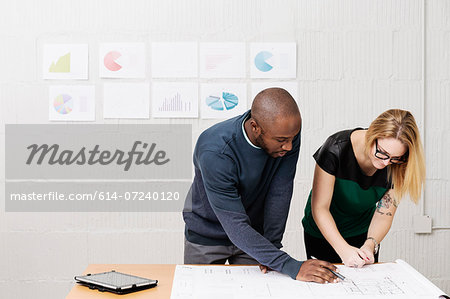 Young business partners working on ideas in design office Stock Photo - Premium Royalty-Free, Image code: 614-07240120