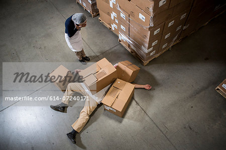 Woman looking at man lying on floor covered by cardboard boxes in warehouse Stock Photo - Premium Royalty-Free, Image code: 614-07240171