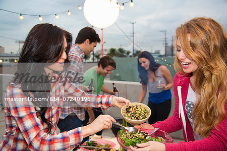 Young adult friends enjoying food at barbeque Stock Photo - Premium Royalty-Free, Image code: 614-07240195