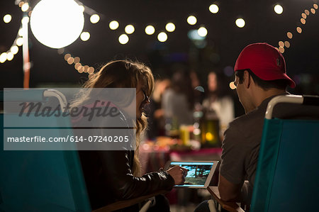 Young couple looking at digital tablet at rooftop barbecue Stock Photo - Premium Royalty-Free, Image code: 614-07240205