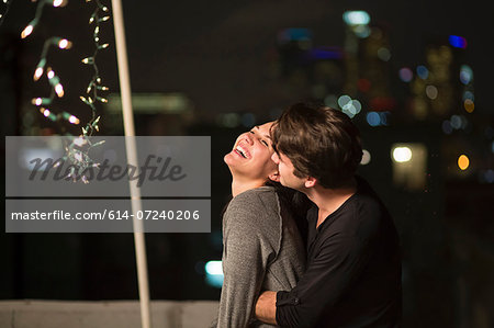 Young couple embracing at rooftop party Stock Photo - Premium Royalty-Free, Image code: 614-07240206
