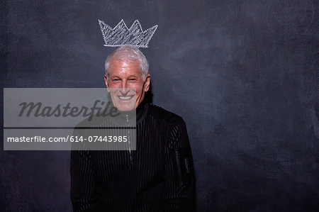 Portrait of senior man in front of chalked crown on blackboard Stock Photo - Premium Royalty-Free, Image code: 614-07443985