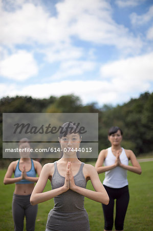 Three young women in park practicing yoga Stock Photo - Premium Royalty-Free, Image code: 614-07444013