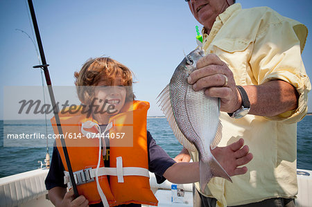 Boy and grandfather with caught fish on boat,  Falmouth, Massachusetts, USA Stock Photo - Premium Royalty-Free, Image code: 614-07444057