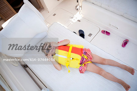 Female toddler hiding in boat wearing lifejacket and sunglasses Stock Photo - Premium Royalty-Free, Image code: 614-07444058