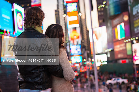 Young couple looking up at neon signs, New York City, USA Stock Photo - Premium Royalty-Free, Image code: 614-07444088
