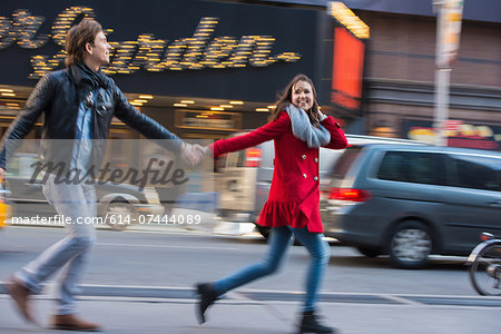 Young couple running along street, New York City, USA Stock Photo - Premium Royalty-Free, Image code: 614-07444089