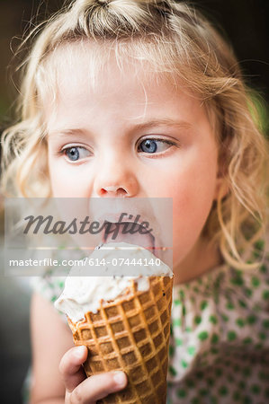Little girl licking an ice cream Stock Photo - Premium Royalty-Free, Image code: 614-07444140