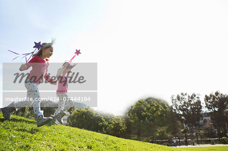 Two young sisters dressed up as fairies running down hill Stock Photo - Premium Royalty-Free, Image code: 614-07444184