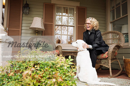 Senior woman sitting on porch rocking chair with dog Stock Photo - Premium Royalty-Free, Image code: 614-07444198