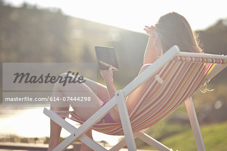 Young woman on deckchair using digital tablet Stock Photo - Premium Royalty-Free, Image code: 614-07444298
