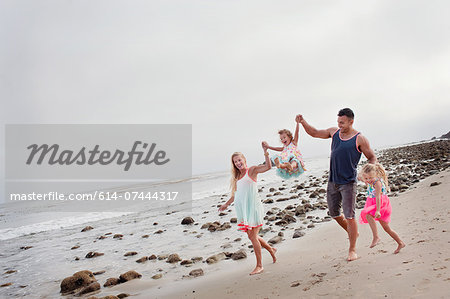 Parents and two young girls walking on beach Stock Photo - Premium Royalty-Free, Image code: 614-07444317
