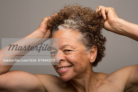Close up studio portrait of senior woman pulling her hair Stock Photo - Premium Royalty-Free, Image code: 614-07444329