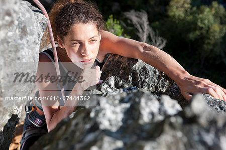 Young female rock climber moving up rock face Stock Photo - Premium Royalty-Free, Image code: 614-07444362