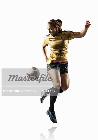 Studio shot of young female soccer player back kicking ball Stock Photo - Premium Royalty-Free, Image code: 614-07444387