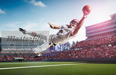 American football player catching ball mid air in stadium Stock Photo - Premium Royalty-Free, Image code: 614-07444390