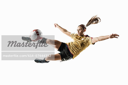 Studio shot of young female soccer player kicking ball mid air Stock Photo - Premium Royalty-Free, Image code: 614-07444392