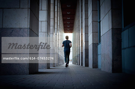 Young man running along urban sidewalk Stock Photo - Premium Royalty-Free, Image code: 614-07453274