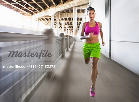 Blurred shot of young woman running on urban bridge Stock Photo - Premium Royalty-Free, Image code: 614-07453278