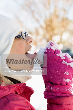 Girl licking snow Stock Photo - Premium Royalty-Free, Image code: 614-07453432