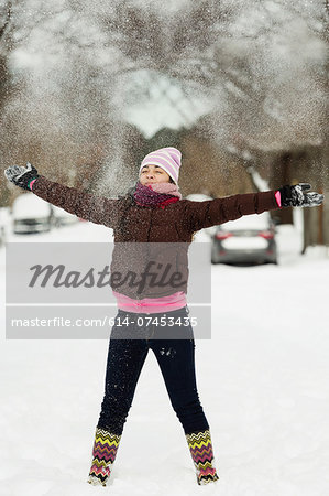 Teenage girl throwing powdered snow mid air in street Stock Photo - Premium Royalty-Free, Image code: 614-07453435