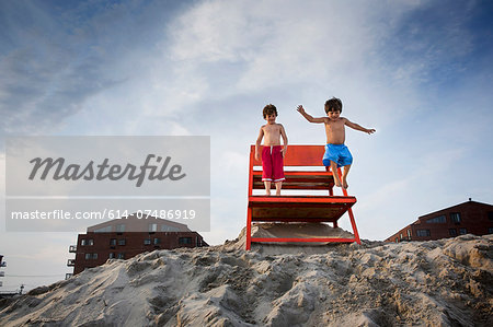 Two boys jumping off red notice board, Long Beach, New York State, USA Stock Photo - Premium Royalty-Free, Image code: 614-07486919