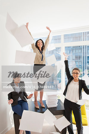 Three young businesswoman throwing papers mid air Stock Photo - Premium Royalty-Free, Image code: 614-07486987