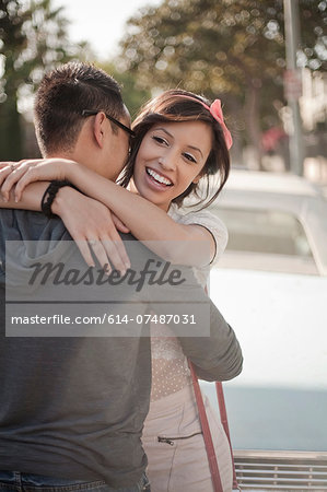 Happy couple hugging on the street Stock Photo - Premium Royalty-Free, Image code: 614-07487031