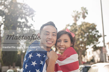 Portrait of a couple standing on street wrapped in American flag Stock Photo - Premium Royalty-Free, Image code: 614-07487035