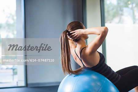 Young woman working out with gym ball Stock Photo - Premium Royalty-Free, Image code: 614-07487110