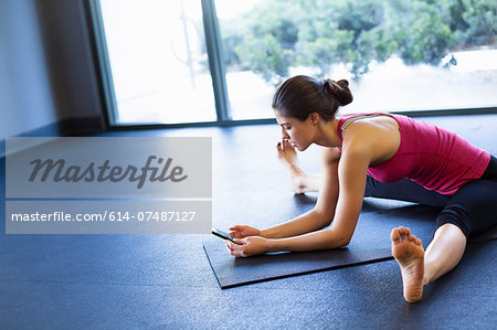 Young woman in yoga posture using cellular phone Stock Photo - Premium Royalty-Free, Image code: 614-07487127