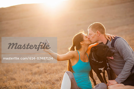 Kissing couple with dog Stock Photo - Premium Royalty-Free, Image code: 614-07487134