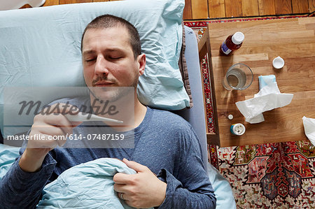 Mid adult man lying in bed looking at thermometer reading Stock Photo - Premium Royalty-Free, Image code: 614-07487159