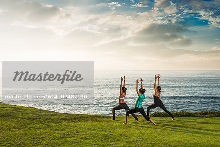 Women on cliff, in yoga position Stock Photo - Premium Royalty-Free, Image code: 614-07487190