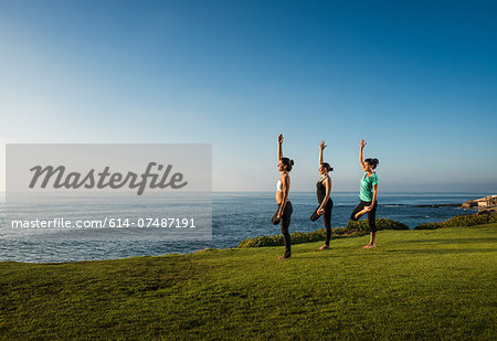 Women on cliff, in yoga positions Stock Photo - Premium Royalty-Free, Image code: 614-07487191