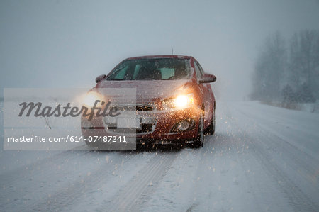 Car with headlights on driving along foggy snow covered road Stock Photo - Premium Royalty-Free, Image code: 614-07487241