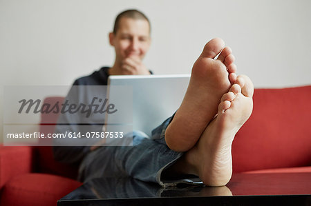Mid adult man relaxing on sofa engrossed in laptop Stock Photo - Premium Royalty-Free, Image code: 614-07587533