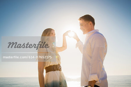 Young couple making a heart in front of sun with hands Stock Photo - Premium Royalty-Free, Image code: 614-07652175