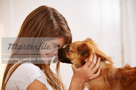 Young woman having face licked by pet dog Stock Photo - Premium Royalty-Free, Image code: 614-07652178