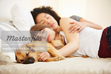 Young female couple and pet dog sleeping on bed Stock Photo - Premium Royalty-Free, Image code: 614-07652182
