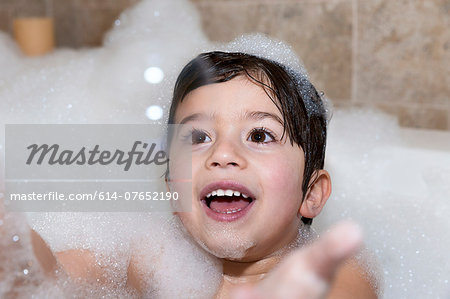 Young boy trying to catch bubble in bubble bath Stock Photo - Premium Royalty-Free, Image code: 614-07652190